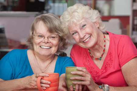 Two happy senior friends with mugs at table