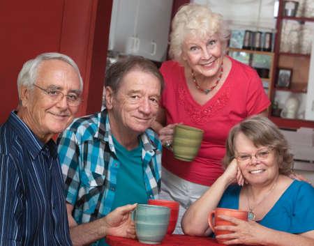 Group of four joyful senior citizens in bistro photo
