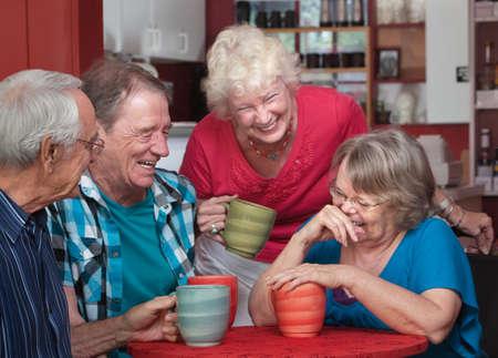 riendo: Grupo de personas mayores que r�en en un caf� Foto de archivo