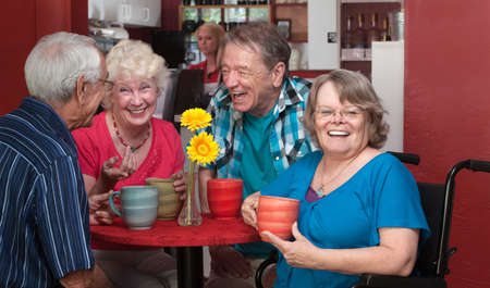 Laughing senior woman in wheelchair with friends in bistro Foto de archivo
