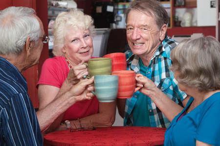 Joyful groep van senior volwassenen roosteren met koffie mokken