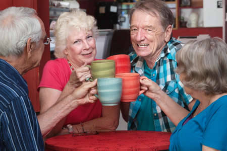 Joyful group of senior adults toasting with coffee mugs photo