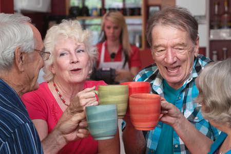 people: Group of four happy seniors with mugs toasting