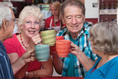 Lachende vrouw met senior vrienden roosteren met koffie mokken Stockfoto