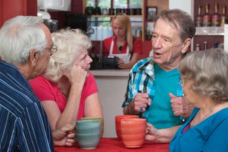 Four Caucasian senior adults with coffee mugs in conversation Фото со стока