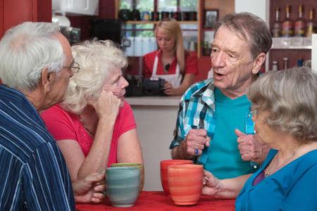 Vier Kaukasische senior volwassenen met koffie mokken in gesprek
