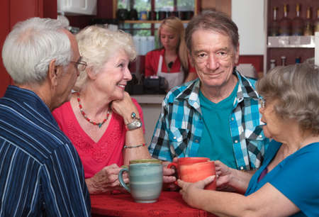 Elderly white adults in a happy conversation at a cafe Foto de archivo