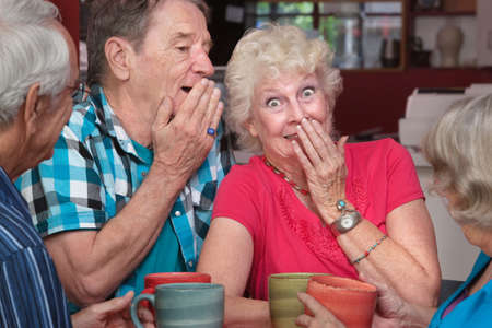Senior man and woman sharing whispering as friends look on