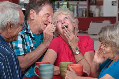 European man whispering to laughing senior woman with friends photo