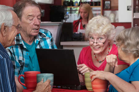 Smiling senior woman with friends pointing at laptop in cafe photo