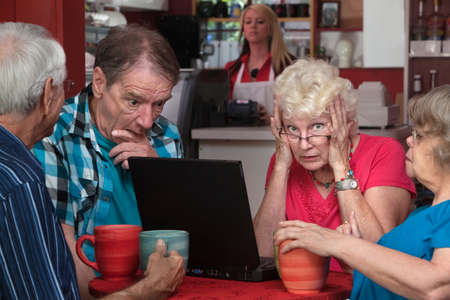 covering: Upset elderly woman with laptop and friends helping Stock Photo