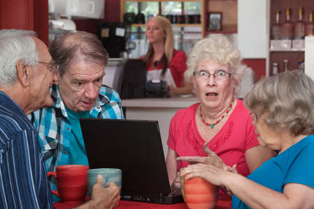 embarrassed: Shocked female senior adult with wide eyes and laptop