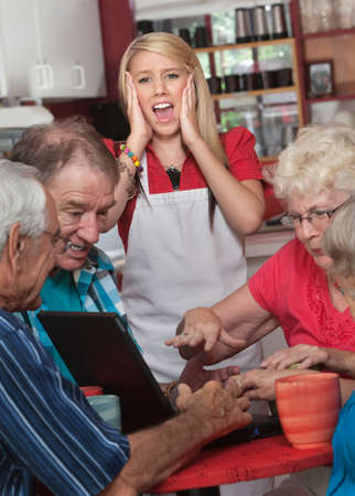 Screaming waitress with upset group of seniors on computer photo