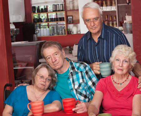senior group: Sad group of four senior citizens in cafe Stock Photo