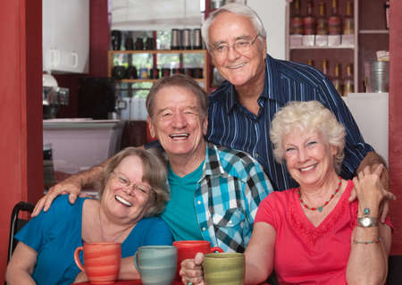 Four senior citizens laughing together in cafe Фото со стока