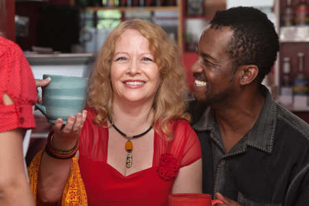 Cheerful African and European couple served coffee photo
