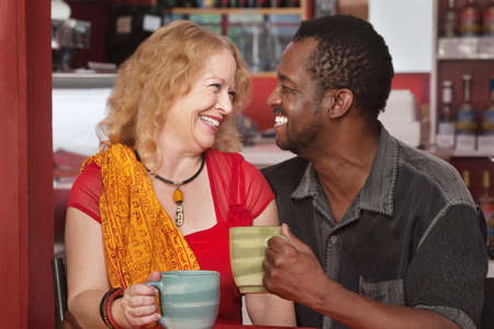Smiling mixed couple with drinks in a cafe photo