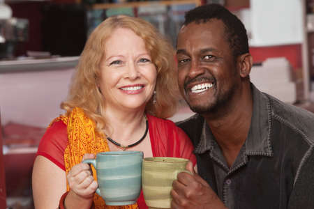 Smiling middle aged husband and wife holding coffee mugs photo