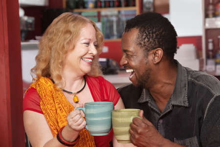 Happy Black man and European woman laughing together in cafe photo