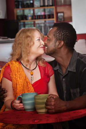 Mixed middle aged couple do an Eskimo Kiss in cafe Stock Photo - 17019862