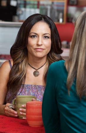 Beautiful Hispanic woman with friend in restaurant Stock Photo - 17019834