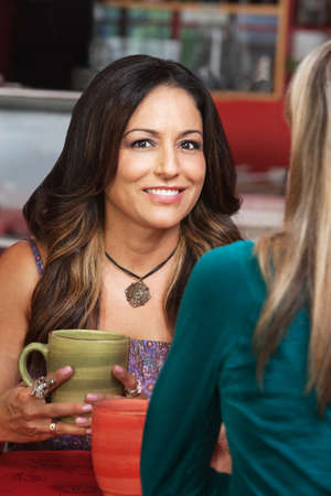 mature mexican: Smiling Mexican woman with friend in cafe Stock Photo