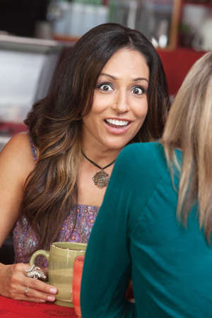 mature mexican: Astonished mature woman talking with friend in coffeehouse