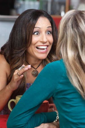 Excited beautiful woman talking to friend in restaurant Stock Photo - 17019798