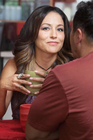 mature mexican: Confident mature Latino woman with man at table Stock Photo