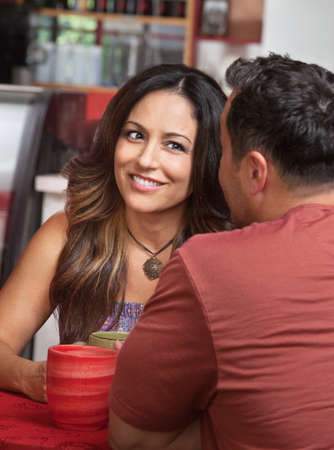Skeptical Hispanic woman listening to man talk in cafe photo