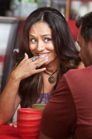 Bashful Hispanic woman across from friend smiling Stock Photo - 17019863