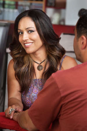 Pretty Native American woman holding husbands hand in restaurant photo