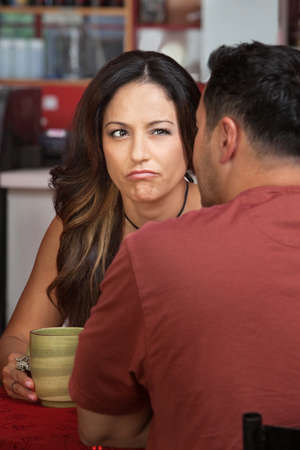 cranky: Doubtful woman looking at man sitting in cafe Stock Photo