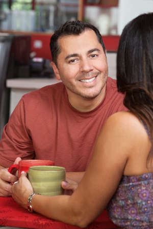 Smiling handsome hispanic man with woman in coffeehouse photo
