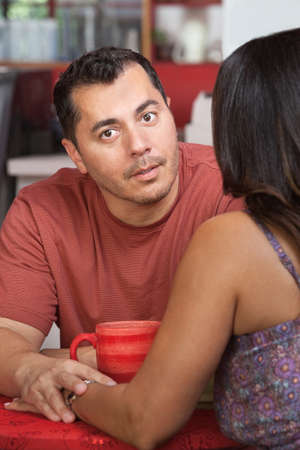 Hispanic man comforting female and holding her hand in cafe photo