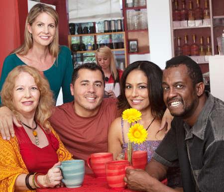 Groep van 5 lachende mensen in coffehouse