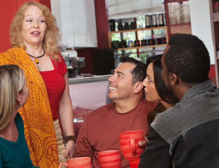 mature mexican: Mature Caucasian female talking with diverse group in cafe Stock Photo