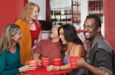 Smiling Black man drinking coffee with group of friends photo