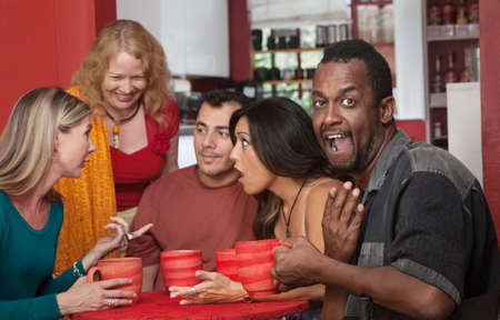 Surprised Black man with group of gossiping friends photo