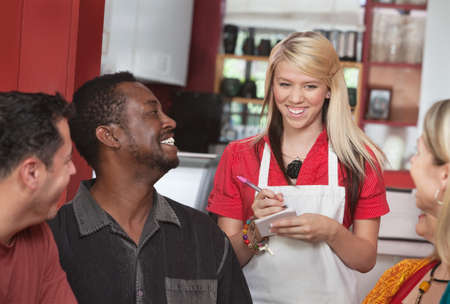 Teenage waitress taking orders from smiling patrons in cafe photo