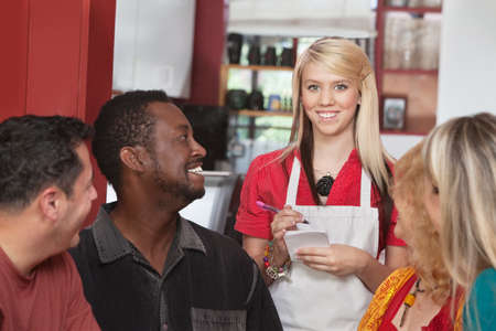 Caucasian waitress taking orders from diverse group of customers photo