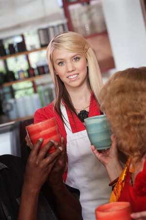 Smiling teenage waitress hands mugs to customers in restaurant Stock Photo - 17019824