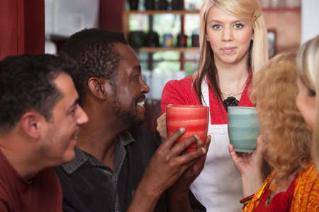 Hostess bringing drinks to customers in coffeehouse photo