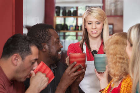 Diverse group of customers with mugs and restaurant attendant photo