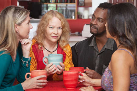 sympathetic: Mature European woman with sympathetic friends in coffeehouse