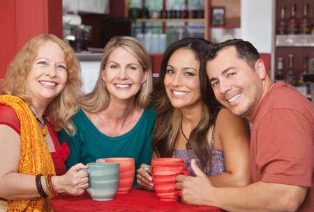 Vier Spaanse en Kaukasische vrienden aan tafel in cafe