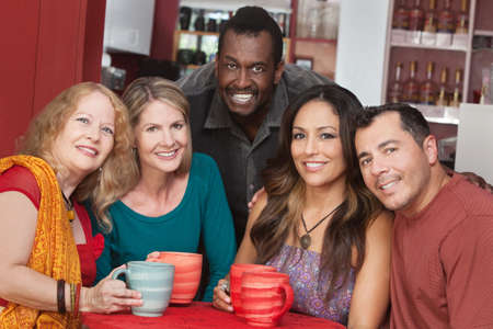 Diverse group of smiling mature adults in restaurant photo