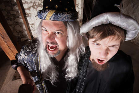 Caucasian father and son dressed as wizards shouting