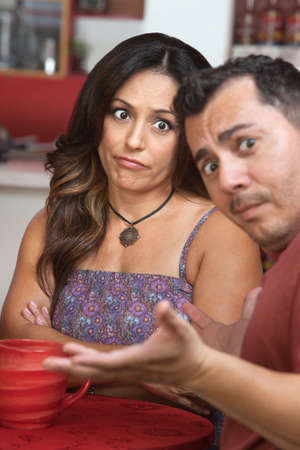 Skeptical Latino woman sitting with man at table