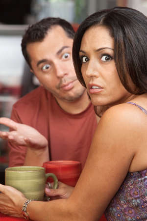 embarrassed: Embarrassed woman arguing a in a restaurant with man Stock Photo